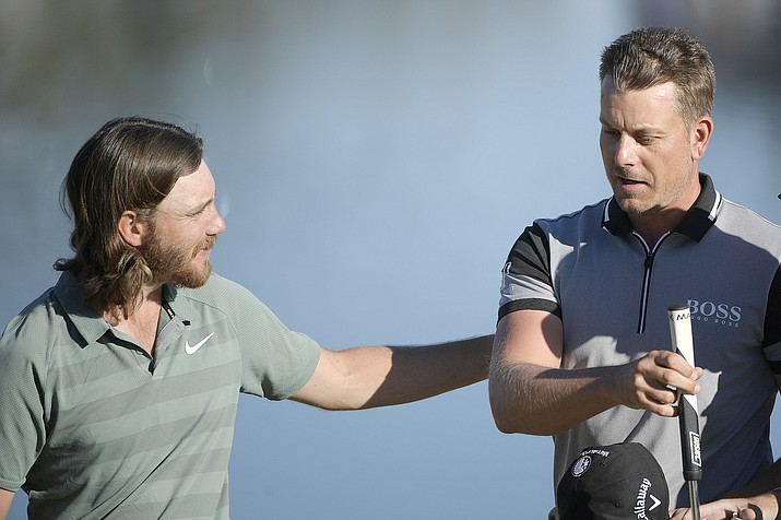 Tommy Fleetwood, left, congratulates Henrik Stenson after putting on the 18th green during the first round of the Arnold Palmer Invitational golf tournament Thursday, March 15, 2018, in Orlando, Fla.