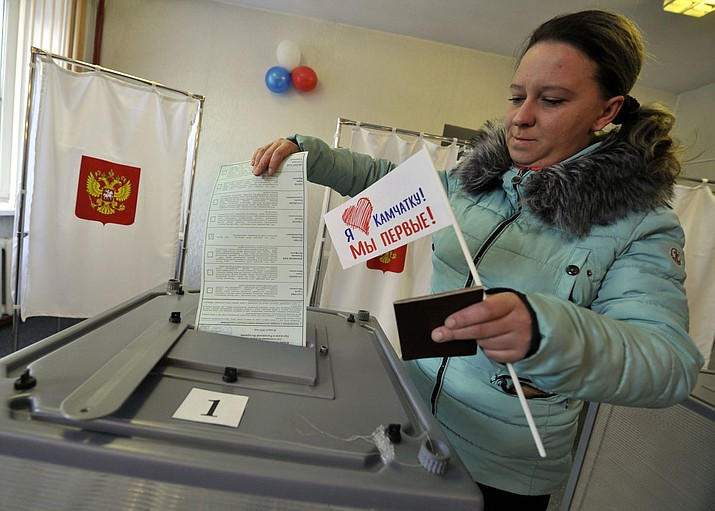 "A woman holds a flag that reads ""I love Kamchatka, we are the first!"" as she prepares to cast her ballots at a polling station in Yelizovo, about 30 kilometers ( 19 miles) north-east from Petropavlovsk-Kamchatsky, capital of Kamchatka Peninsula region, Russian Far East, Russia, on Sunday, March. 18, 2018. Polls have opened in Russia's Far East regions for the presidential election in which Vladimir Putin is seeking a fourth term in the Kremlin. (AP Photo/Alexander Petpov)"