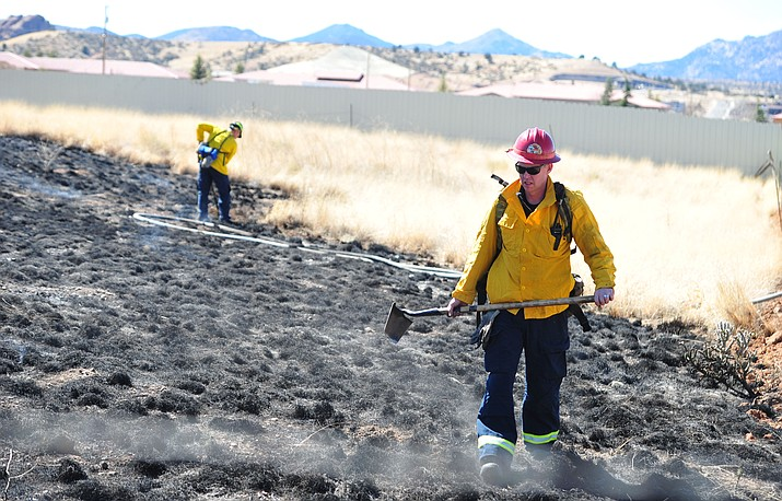 Prescott firefighters put out spots in a wildland fire along Side Road in Prescott Monday, March 19, 2018. (Les Stukenberg/Courier)