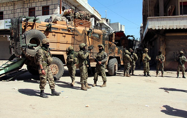 Turkish soldiers, positioned in the city center of Afrin, northwestern Syria, Monday, March 19, 2018, a day after they took the control of the area. Turkey's President Recep Tayyip Erdogan said Monday following victory in Syria's Afrin region, his country will expand its military operations into other Kurdish-held areas in Syria as well as in Iraq's Sinjar region.(Hasan Kırmızitaş/DHA-Depo Photos via AP)