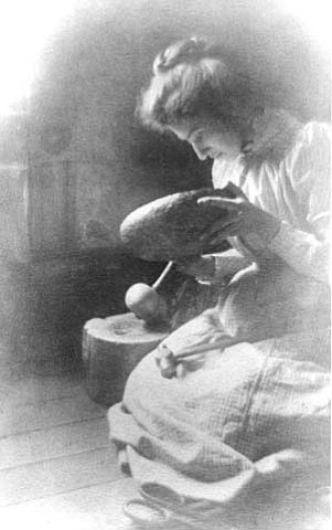 MARY COLTER AT AGE 23 MAKING A METAL BOWL. WEARING CALICO DRESS. SOFT FOCUS. CIRCA 1892.