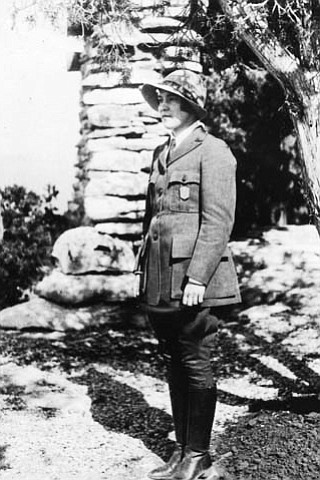 PAULINE / POLLY PATRAW, FIRST WOMAN RANGER NATURALIST AT GRCA. STANDING IN HER UNIFORM BY YAVAPAI OBSERVATION STATION. CIRCA 1930. NPS.