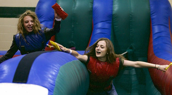 Former Prescott High School graduates Allie Jo Amos and Grace Doyle enjoy their time on a bouncy slide at the 2017 Grad Night Party on May 26, 2017, at the YMCA in Prescott. (Courtesy)