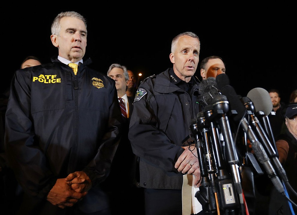 Interim Austin Police Chief Brian Manley, right, stands with other members of law enforcement as he briefs the media, Wednesday, March 21, 2018, in the Austin suburb of Round Rock, Texas. The suspect in a spate of bombing attacks that have terrorized Austin over the past month blew himself up with an explosive device as authorities closed in, the police said early Wednesday. (AP Photo/Eric Gay)
