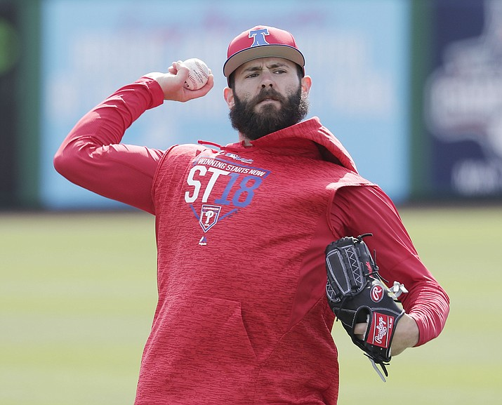 Philadelphia Phillies pitcher Jake Arrieta, in this March 13, 2018, file photo, throws during a workout before a spring baseball exhibition game against the Tampa Bay Rays, in Clearwater, Fla. When free-agent ace Jake Arrieta arrived at spring training on co-owner John Middleton's private plane, it signaled the start of a new era for this franchise. (AP Photo/John Raoux, File)