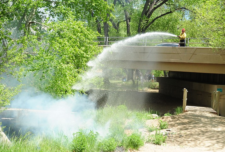 Prescott firefighters extinguish a wildland fire under the LaGuardia Bridge near Granite Creek Park on April 27, 2016, in Prescott. Highly flammable cottonwood 'cotton' was ignited. The ban on smoking in city parks, in part, is in response to fire risks. (Les Stukenberg/Courier, File)