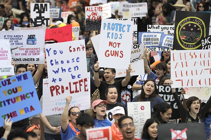 """Crowds of people hold signs on Pennsylvania Avenue at the """"March for Our Lives"""" rally in support of gun control, Saturday, March 24, 2018, in Washington. (AP Photo/Alex Brandon)"""