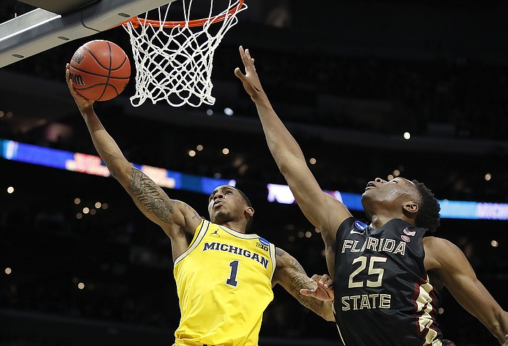 Michigan guard Charles Matthews (1) shoots against Florida State forward Mfiondu Kabengele (25) during the first half of an NCAA men's college basketball tournament regional final Saturday, March 24, 2018, in Los Angeles. (Jae Hong/AP)