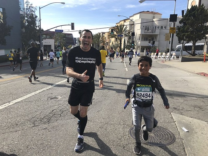 In this March 18, 2018, photo provided by Pash Pashkow, movie production lawyer Loren Zitomersky, left, runs the Los Angeles Marathon backward as a young runner briefly accompanies him. Zitomersky has embarked on a singular, if odd, quest: At the 2018 Boston Marathon, he'll attempt to break the world record for running the distance backward. Zitomersky is trying to raise money and awareness for a cure for epilepsy. (Pash Pashkow via AP)