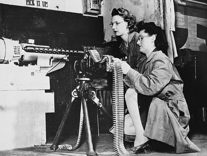 In this April 30, 1943, file photo, Mae Zelisnky shoots as Betty O'Beda feeds a 30-caliber rifle during an ammunition test at Remington Arms Company. The gun was fired down an enclosed range into a sand pit. (AP Photo, File)