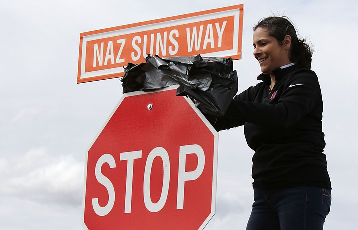 Northern Arizona Suns director of business operations Ashley Stovall unveils the NAZ Suns Way sign Saturday, March 24, 2018, in Prescott Valley. The new name of the road recognizes the Prescott Valley-based, minor league affiliate of the NBA's Phoenix Suns. The road was previously named Sundogs Blvd., for the Arizona Sundogs hockey team, formerly based in Prescott Valley. (Matt Hinshaw/NAZ Suns)