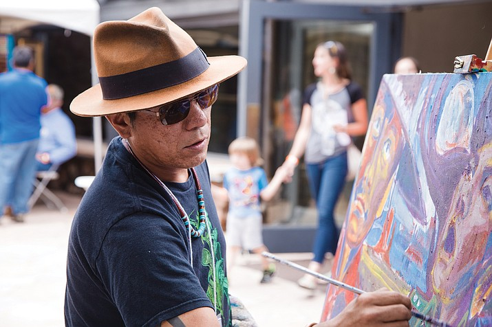 "Bahe Whitethorn, Jr. works on a painting in the courtyard of the Museum of Northern Arizona during the 67th annual Navajo Festival of Arts & Culture. He earned an Honorable Mention for his painting ""Warriors Gaze."" (Photo/Ryan Williams Photography)"
