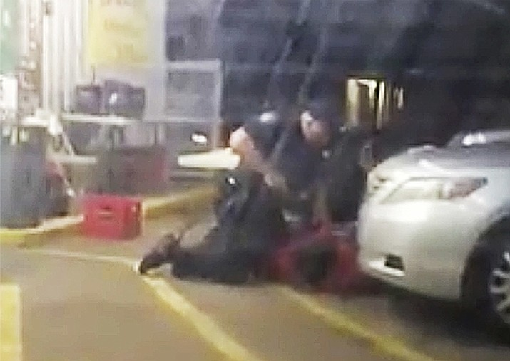In this July 5, 2016 image made from video, Alton Sterling is restrained by two Baton Rouge police officers, one holding a gun, outside a convenience store in Baton Rouge, La. Moments later, one of the officers shot and killed Sterling, a black man who had been selling CDs outside the store, while he was on the ground. Louisiana's attorney general has ruled out criminal charges against the two white officers in the fatal shooting of Sterling. (Arthur Reed)