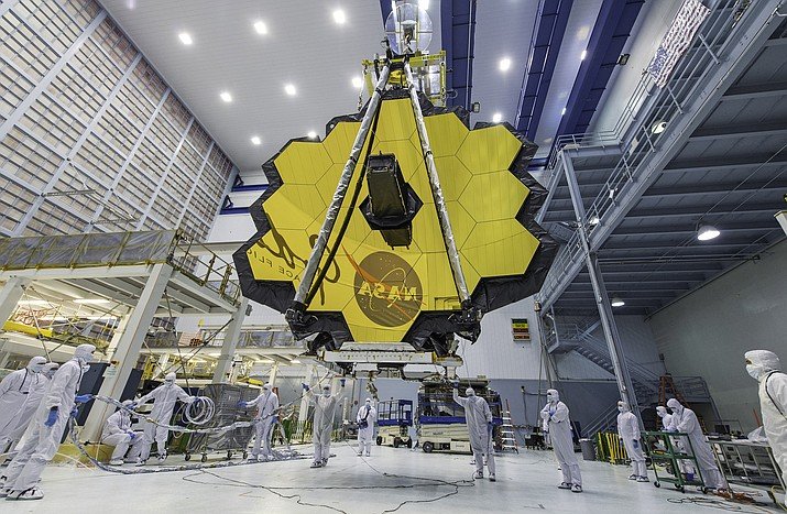 In this April 13, 2017 photo provided by NASA, technicians lift the mirror of the James Webb Space Telescope using a crane at the Goddard Space Flight Center in Greenbelt, Md. The telescope's 18-segmented gold mirror is specially designed to capture infrared light from the first galaxies that formed in the early universe. On Tuesday, March 27, 2018, NASA announced it has delayed the launch of the next-generation space telescope until 2020. (Laura Betz/NASA)