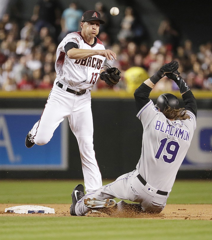 Arizona Diamondbacks' Nick Ahmed (13) forces out Colorado Rockies' Charlie Blackmon (19) as he turns a double play on DJ LeMahieu during the fifth inning of a baseball game Thursday, March 29, 2018, in Phoenix. The Diamondbacks dominated the Rockies — winning 8-2. (AP Photo/Matt York)