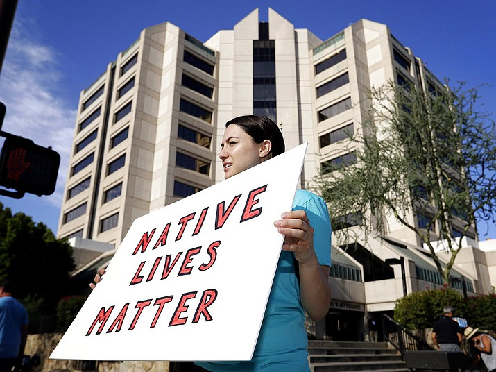 In this July 25, 2016, file photo, Heather Hamel protests outside Maricopa County Attorney Bill Montgomery's office, in Phoenix. The Navajo Nation has sued the federal government and the city of Winslow, Ariz., over the death of a scissors-wielding tribal member shot by a police officer for the northern Arizona city. (AP Photo/Matt York, file)
