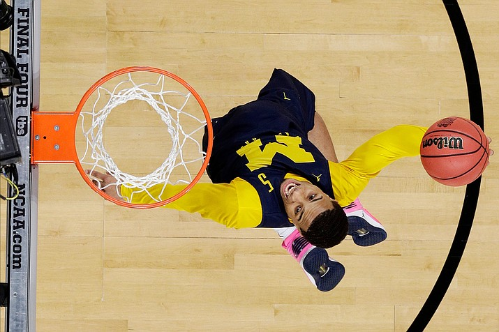 Michigan guard Jaaron Simmons dunks the ball during a practice session for the Final Four NCAA college basketball tournament, Friday, March 30, 2018, in San Antonio. (AP Photo/David J. Phillip)