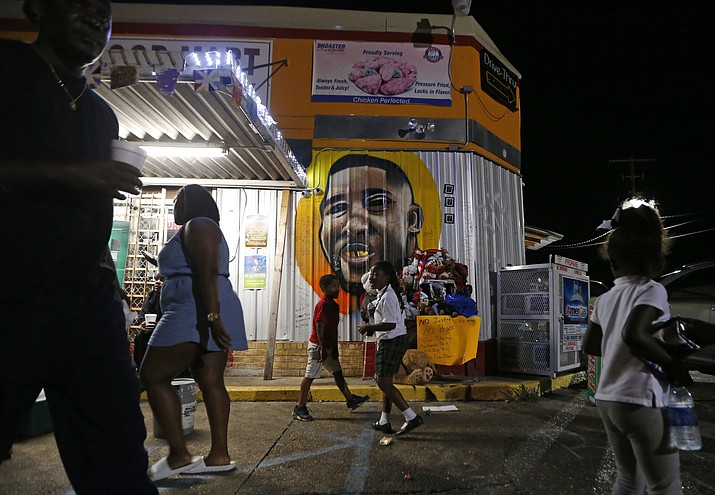 In this May 2, 2017, file photo, people congregate in front of a mural of Alton Sterling outside the Triple S Food Mart, where Sterling was killed in 2016, in Baton Rouge, La. The investigation of the deadly police shooting that inflamed racial tensions in Louisiana's capital city has ended without criminal charges against two white officers who confronted Sterling, a black man outside a convenience store two summers ago. Experts in police tactics think the bloodshed could have been avoided if the Baton Rouge officers had done more to defuse the encounter with Sterling. They say poor police tactics and techniques may have aggravated the volatile confrontation, which lasted less than 90 seconds. (AP Photo/Gerald Herbert, File)