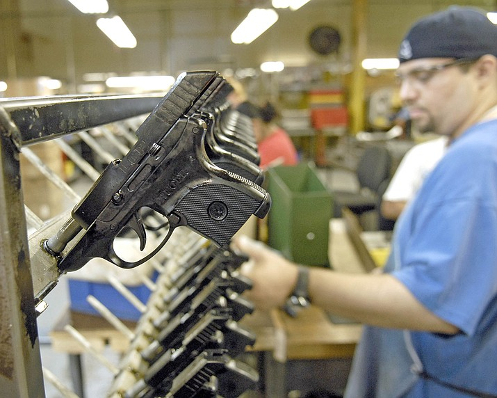 Dirkson Davis, lead assembler completes each pistol and places the Light Compact Pistol on a rack for the next phase of production. (Courier file photo)
