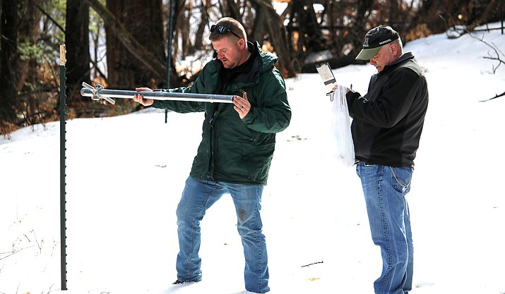 Two USDA-NRCS engineers measure snow pack near Pine. (Photo by Casey Kuhn/KJZZ)