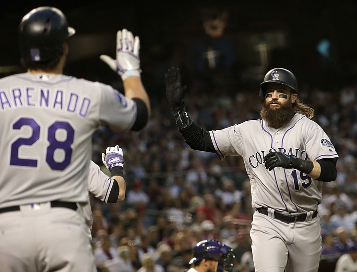 Colorado Rockies' Charlie Blackmon (19) celebrates with Nolan Arenado (28) after hitting a solo home run against the Arizona Diamondbacks during the sixth inning Saturday, March 31, 2018, in Phoenix. (Matt York/AP)