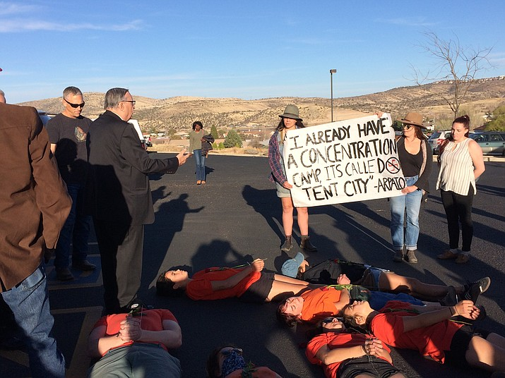 """Joe Arpaio, left, tries to engage student protesters in conversation as they conduct a """"die-in"""" outside the Rowle Simmons Adult Center on Friday, March 30, in Prescott. The students were calling attention to inmates who died while in custody in the Maricopa County jail system under former Sheriff Arpaio's leadership. (Sue Tone/Courier)"""