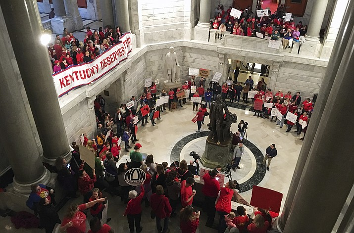 Hundreds of Kentucky teachers protest outside of Gov. Matt Bevin's office on Friday, March 30, 2018, in Frankfort, Ky. State lawmakers passed a bill late Thursday night that makes changes to the state's pension system. Bevin could sign the bill into law on Friday. (AP Photo/Adam Beam)