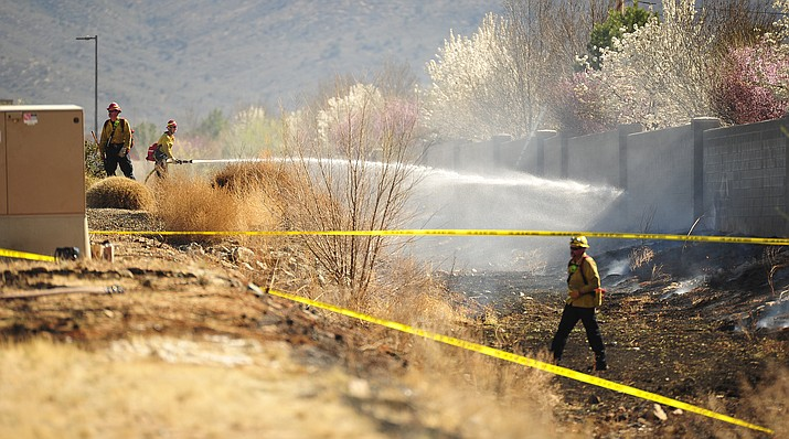 Central Arizona firefighters put out a wildland fire in the drainage behind the Walmart on Glassford Hill Road in Prescott Valley Friday, March 30, 2018. (Les Stukenberg/Courier)