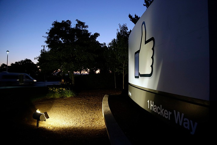 "In this Jun 7, 2013, file photo, the Facebook ""like"" symbol is illuminated on a sign outside the company's headquarters in Menlo Park, Calif. Australian authorities say they are investigating whether Facebook breached the country's privacy law when personal information of more than 300,000 Australian users was obtained by Cambridge Analytica, a Trump-linked political consulting firm, without their authorization. (AP Photo/Marcio Jose Sanchez, File)"