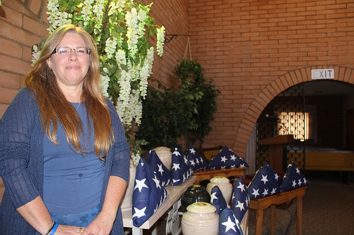 Jamie Zorn, of Sutton Memorial Funeral Home in Kingman, stands by American flags that go with 15 urns and boxes containing the unclaimed cremated remains of U.S. military veterans that will be escorted Friday by Patriot Guard Riders to Prescott National Cemetery.