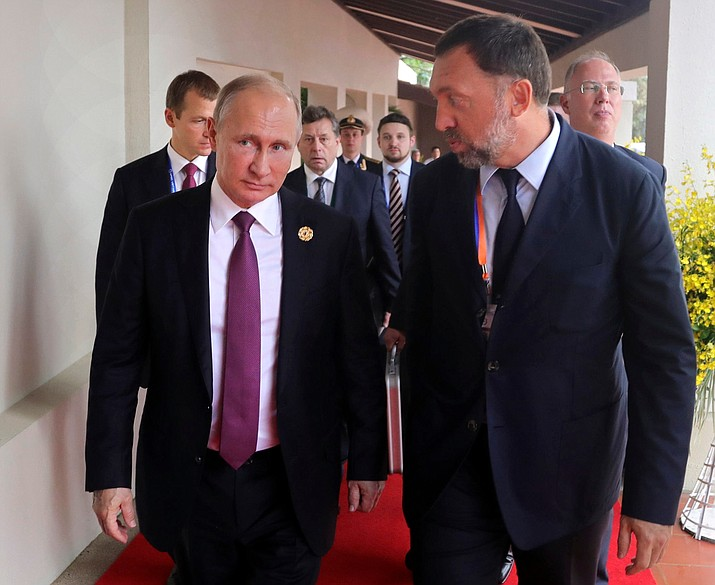 This Nov. 10, 2017, file photo shows Russia's President Vladimir Putin, left, and Russian metals magnate Oleg Deripaska, right, walking to attend the APEC Business Advisory Council dialogue in Danang, Vietnam. The United States punished dozens of Russian oligarchs and government officials on Friday, April 6, 2018, with sanctions that took direct aim at President Putin's inner circle, as President Donald Trump's administration tried to show he's not afraid to take tough action against Moscow. Seven Russian tycoons, including aluminum magnate Deripaska, were targeted, along with 17 officials and a dozen Russian companies, the Treasury Department said. (Mikhail Klimentyev, Sputnik, Kremlin Pool Photo)