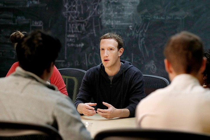 "In this Nov. 9, 2017, file photo, Facebook CEO Mark Zuckerberg meets with a group of entrepreneurs and innovators during a round-table discussion in St. Louis. Facebook said Wednesday, April 5, 2018, that it has shut down a feature that let people search for Facebook users if they had their phone number or email address. In a call with reporters on Wednesday, Zuckerberg said the company had tried ""rate limiting"" the searches. (AP Photo/Jeff Roberson, File)"