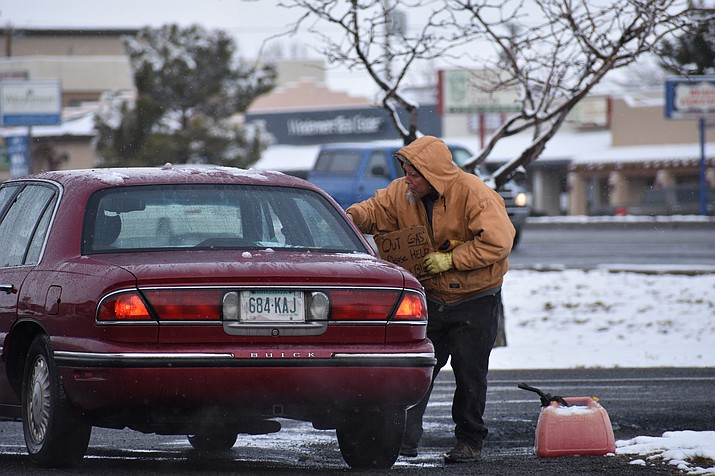 "A panhandler collects money from a motor vehicle after the driver stopped at an intersection Feb. 22, 2018, in Prescott Valley. The unidentified panhandler holds a sign that reads, ""Out Gas ... Please Help ... God Bless."" (Richard Haddad/WNI)"