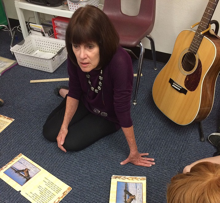 Abia Judd Elementary second-grade teacher Jane Robertson reads with a group of students next to her ever-present acoustic guitar. (Nanci Hutson/Courier)