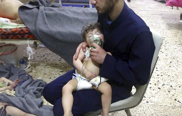 A medical worker gives a toddler oxygen through respirators following an alleged poison gas attack in the opposition-held town of Douma, in eastern Ghouta, near Damascus, Syria, Sunday, April 8, 2018. (Image from video provided by Syrian Civil Defense White Helmets)