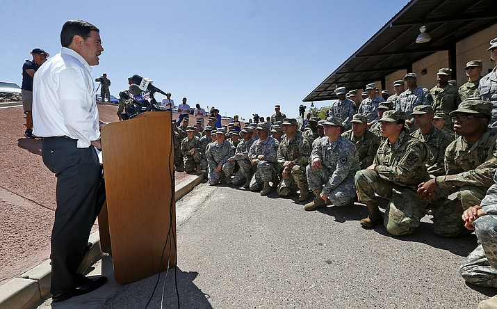 Arizona Republican Gov. Doug Ducey speaks to Arizona National Guard soldiers prior to deployment to the Mexico border at the Papago Park Military Reservation, Monday, April 9, 2018, in Phoenix. Ducey said Monday that 225 members of the state's National Guard were heading to the U.S.-Mexico border to support President Donald Trump's call for troops to fight drug trafficking and illegal immigration. (AP Photo/Ross D. Franklin)