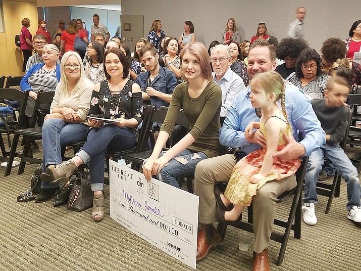 Bradshaw Mountain High School junior MaKenna Farrell sits with her family at the Youth Art Month exhibit March 28 with a representational check for $1,000 worth of art supplies for her prize-winning design. (Courtesy image)