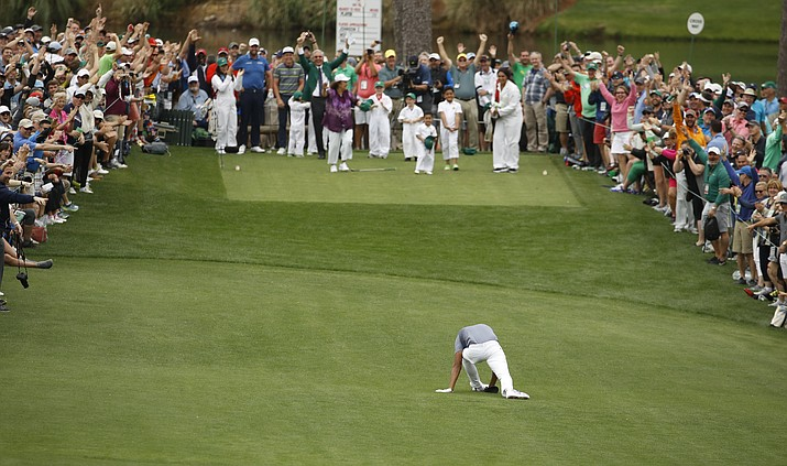 Tony Finau appears to twist his ankle after reacting to his hole in one on the seventh hole during the par-three competition at the Masters golf tournament Wednesday, April 4, 2018, in Augusta, Ga. (AP Photo/Charlie Riedel)