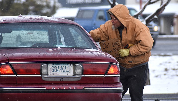 A local man solicits help from passing drivers during a snowy day in 2018. The City of Prescott will soon begin installing signs at busy Prescott corners, urging passers-by not to give to panhandlers. As an alternative, the signs will suggest donating to a city-led effort to collect money toward helping the homeless. (Richard Haddad/WNI)