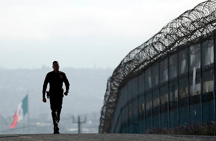 In this June 22, 2016 file photo, Border Patrol agent Eduardo Olmos walks near the secondary fence separating Tijuana, Mexico, background, and San Diego in San Diego. California Gov. Jerry Brown agreed Wednesday, April 11, 2018, to deploy 400 National Guard troops at President Donald Trump's request, but not all will head to the U.S.-Mexico border as Trump wants and none will enforce federal immigration enforcement. (AP Photo/Gregory Bull, File)