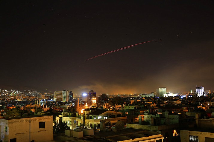 Explosions lit up the skies with anti-aircraft fire, over Damascus, the Syrian capital, as the U.S. launches an attack on Syria targeting different parts of the Syrian capital Damascus, Syria, early Saturday, April 14, 2018. Syria's capital has been rocked by loud explosions that lit up the sky with heavy smoke as U.S. President Donald Trump announced airstrikes in retaliation for the country's alleged use of chemical weapons. (AP Photo/Hassan Ammar)