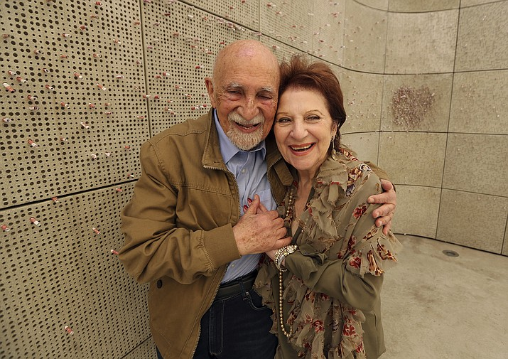 In this Wednesday, April 11, 2018, photo, childhood Holocaust survivors Simon Gronowski and Alice Gerstel Weit talk as they are interviewed at the Los Angeles Holocaust Museum, after their reunion after more than 70 years. There was much hugging, kissing and crying Wednesday as the two old friends held hands tightly while sitting outside on a museum patio to share memories from a long-ago past. (AP Photo/Reed Saxon)