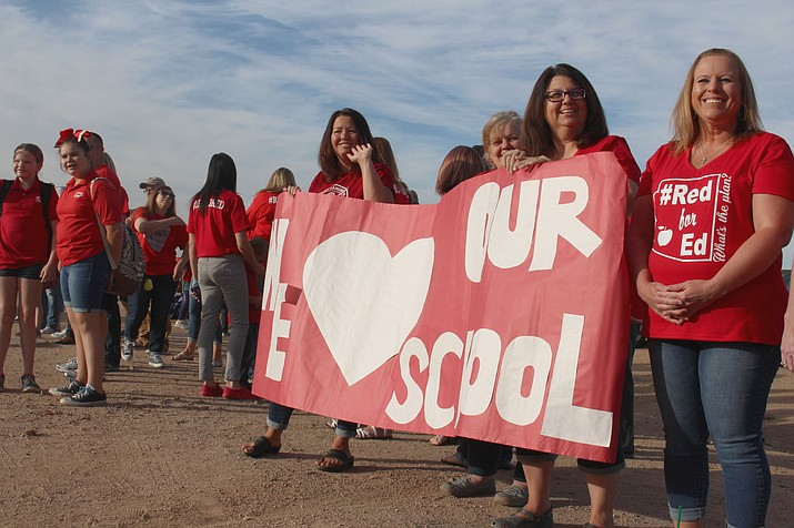"Teachers outside Kingman Academy High School holding up a banner that says ""We love our school"" as cars pass by to drop off students for school. (Photo by Vanessa Espinoza/Daily Miner)"