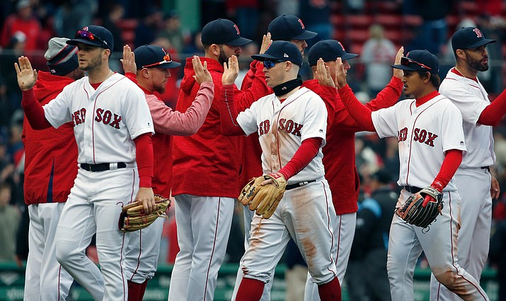 Boston Red Sox players, from left foreground, Andrew Benintendi, Brock Holt and Tzu-Wei Lin celebrate after defeating the Baltimore Orioles in a baseball game in Boston on Saturday, April 14, 2018. (Michael Dwyer/AP)