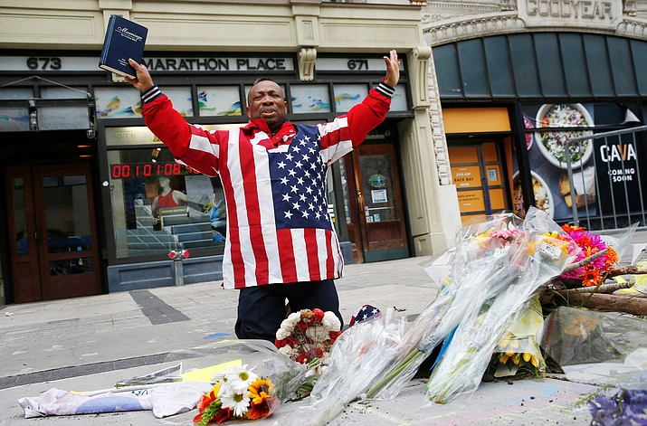 Cristopher Nzenwa, of Boston, prays at the site of the first explosion during the 2013 Boston Marathon, Sunday, April 15, 2018, in Boston. (Michael Dwyer/AP)