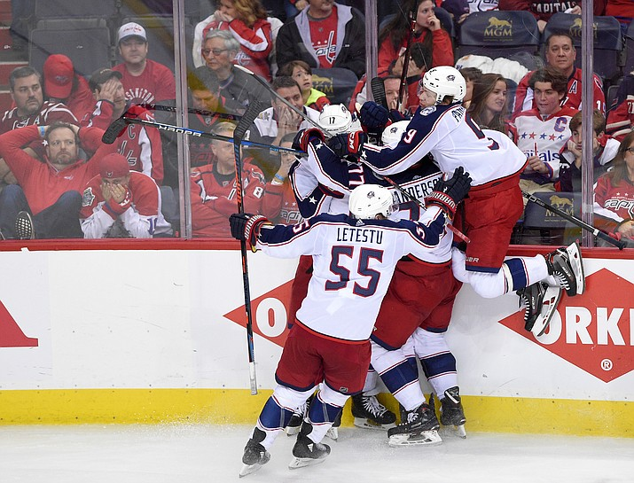 Columbus Blue Jackets left wing Matt Calvert, obscured, celebrates his game-winning goal with Artemi Panarin (9), Mark Letestu (55), Josh Anderson (77), Brandon Dubinsky (17) during overtime in Game 2 of an NHL first-round hockey playoff series against the Washington Capitals on Sunday, April 15, 2018, in Washington. The Blue Jackets won 5-4 in overtime. (Nick Wass/AP)
