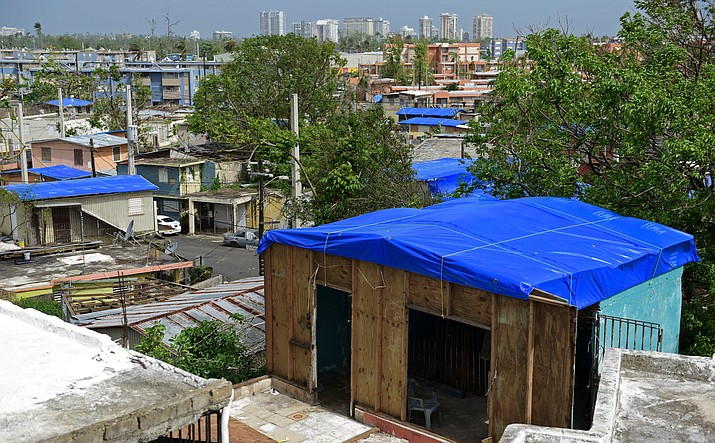 In this Oct. 19, 2017, file photo, homes in the Cantera area are covered with tarps provided by the Federal Emergency Management Agency. In the distance, buildings from the Hato Rey area stand in the background, in San Juan, Puerto Rico. (AP Photo/Carlos Giusti, File)