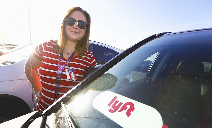 "In this Wednesday, April 11, 2018, photo, Stefanie Lowe, a teacher at Tuscano Elementary School, stands next to her car in the parking lot after joining other teachers, parents and students as they stage a ""walk-in"" for higher pay and school funding in Phoenix. To help make ends meet, Lowe is a Lyft driver. In Arizona, teachers are paid some of the lowest wages in the country. (Ross D. Franklin/AP)"