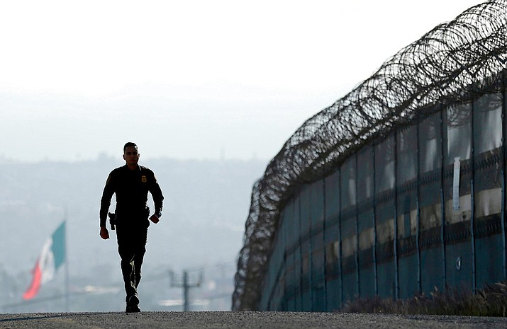 In this June 22, 2016 file photo, a border patrol agent walks near the secondary fence separating Tijuana, Mexico, background, and San Diego in San Diego. California has rejected the federal government's initial plans for National Guard troops to the border because the work is considered too closely tied to immigration enforcement. (AP Photo/Gregory Bull, File)