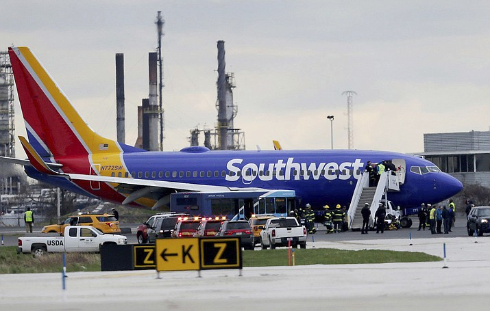 A Southwest Airlines plane sits on the runway at the Philadelphia International Airport after it made an emergency landing in Philadelphia, on Tuesday, April 17, 2018. (David Maialetti/The Philadelphia Inquirer via AP)